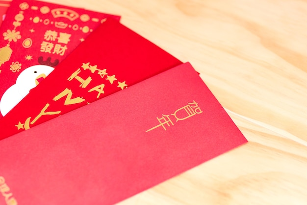 Pacote de envelope vermelho ano novo chinês, hongbao com o personagem 'feliz ano novo' em fundo de madeira para o ano novo chinês. tradução: boa sorte no ano