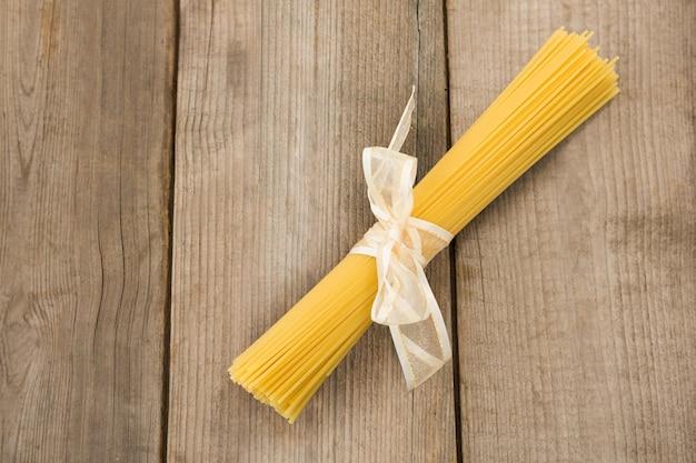 Pacote de espaguete cru amarrado com fita branca na superfície de madeira