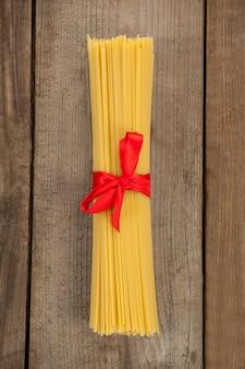 Pacote de espaguete cru amarrado com fita vermelha na superfície de madeira