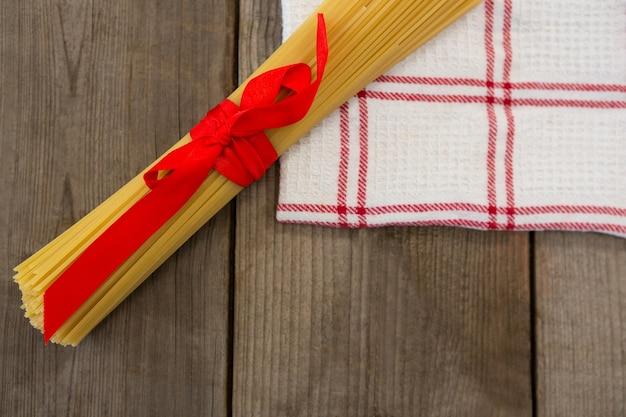Pacote de espaguete cru amarrado com fita vermelha no guardanapo