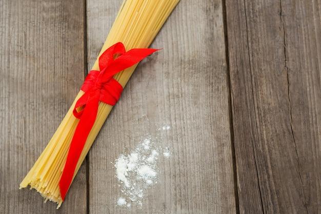 Pacote de espaguete cru e farinha na superfície de madeira