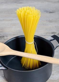 Pacote de espaguete em uma panela preta, pronta para cozinhar