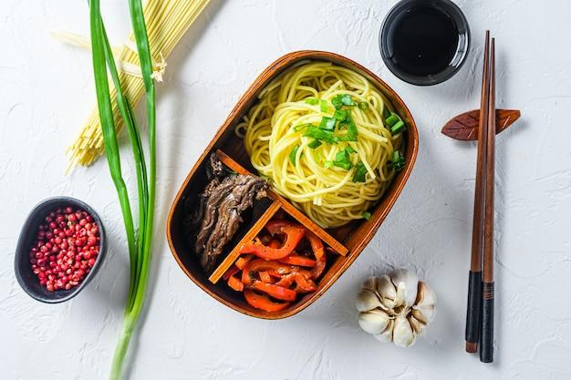 Pacote de lanche bento caseiro, carne grelhada e macarrão com ingredientes da mesa branca vista de cima.