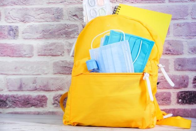 Pacote de mochila escolar com desinfetante e máscara facial.