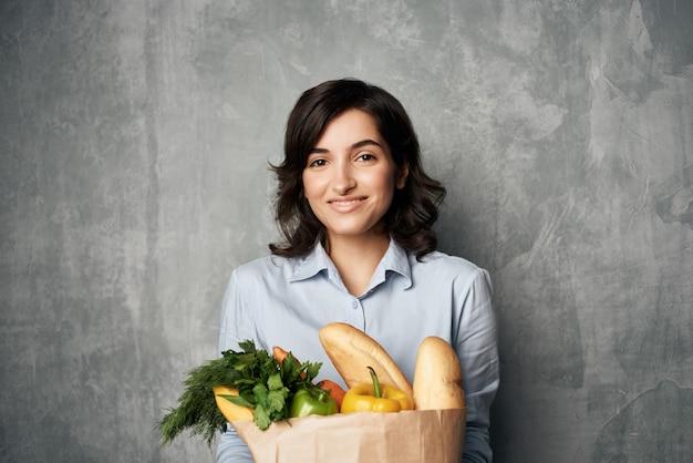 Pacote de mulher sorridente com legumes e verduras, fazendo compras no supermercado