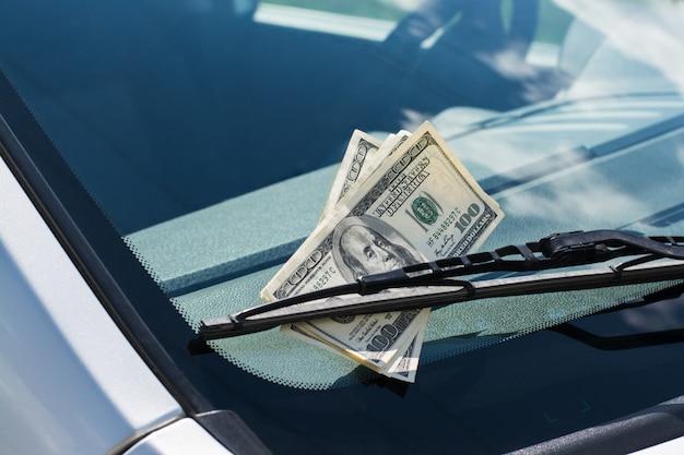 Pacote de notas de dólar dos eua deixadas em um carro sob o limpador de para-brisa do carro