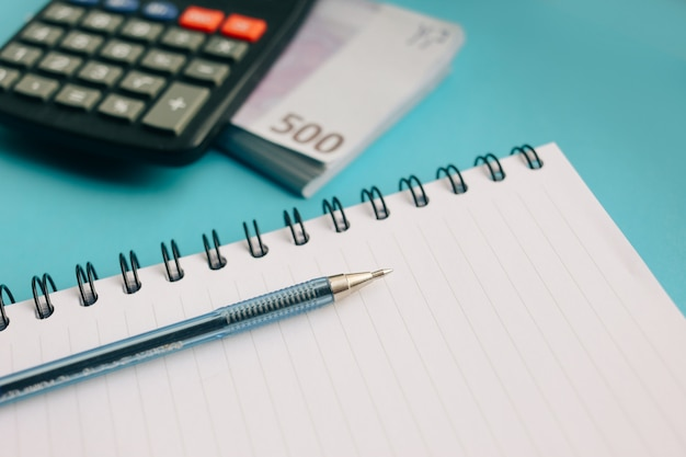 Pacote de notas de euro e uma calculadora em um fundo azul