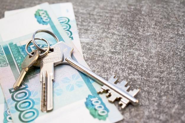 Pacote de notas do dinheiro do russo mil rublos e três chaves da casa no fundo concreto.