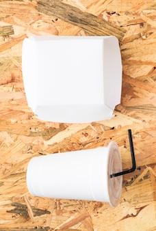 Pacote de papel branco e bebida descartável no pano de fundo texturizado