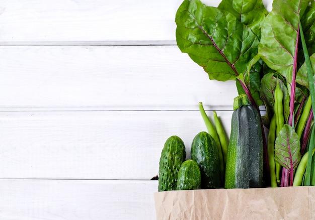 Pacote de papel cheio de legumes verdes frescos