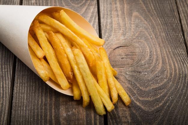 Pacote de papel com batatas fritas em fundo de madeira