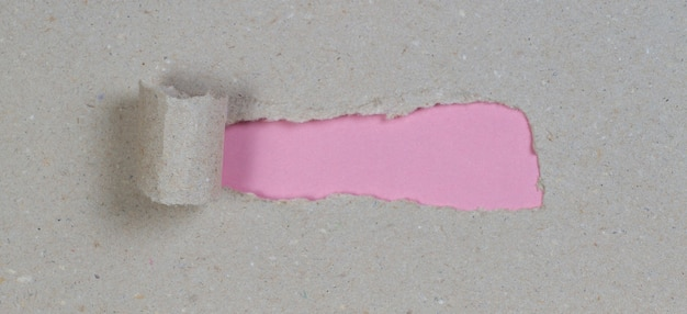 Pacote de papel marrom rasgado para revelar parede rosa com espaço de cópia