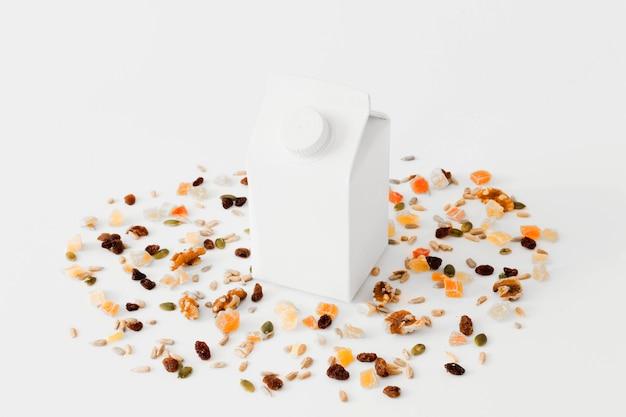 Pacote de papelão branco entre frutas secas e nozes