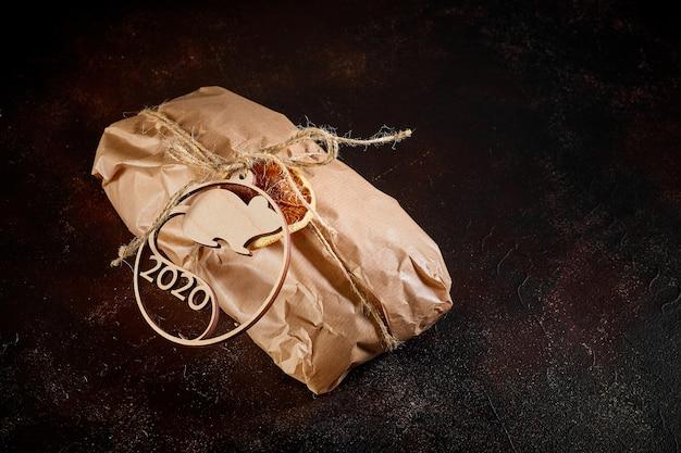 Pacote de presente de papel kraft amarrado com barbante com o emblema do ano novo símbolo mouse feito de madeira compensada