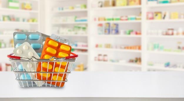 Pacote de remédios na cesta de compras com prateleiras da farmácia e drogaria desfocar o fundo