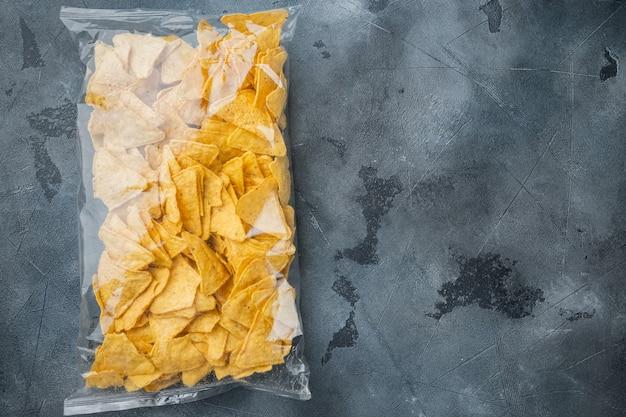 Pacote de salgadinhos de milho, em mesa cinza, vista superior ou disposição plana