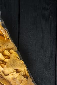 Pacote de salgadinhos de milho, em mesa de madeira preta, vista de cima ou plano