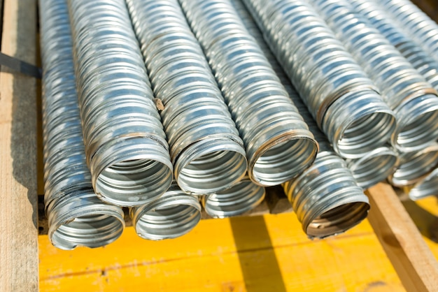 Pacote de tubos de metal corrugado em um canteiro de obras, close-up