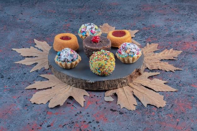 Pacote de vários bolos em uma placa de madeira.
