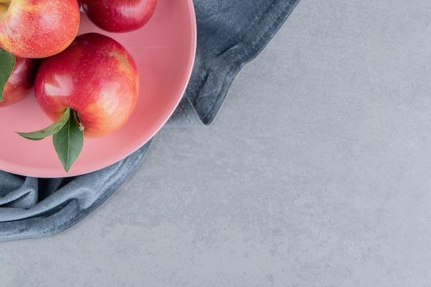 Pacote delicioso de maçãs em uma bandeja rosa no mármore.