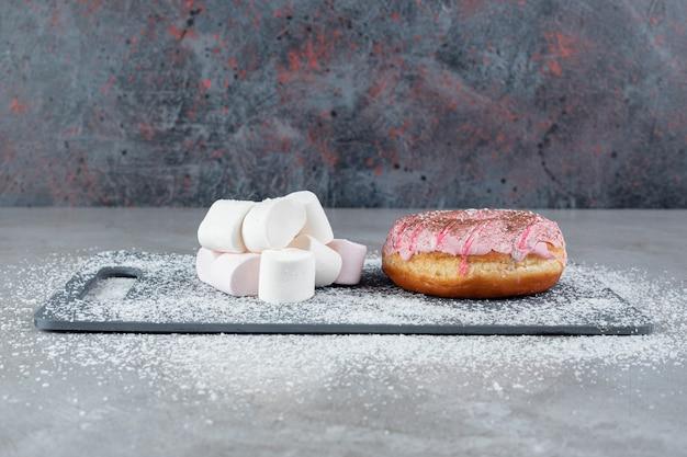 Pacote doce de marshmallows e uma rosquinha em um tabuleiro coberto com pó de coco na superfície de mármore