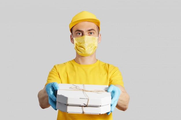 Pacote para a porta. correio em uniforme amarelo, máscara protetora e luvas oferece pizza e café para viagem. serviço de entrega em quarentena.