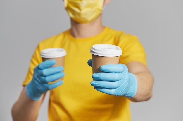 Pacote para a porta. courier em uniforme amarelo, máscara protetora e luvas oferece café para viagem. serviço de entrega em quarentena.