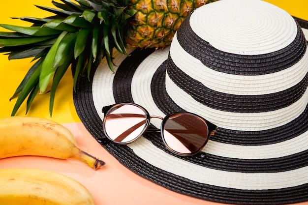 Pacote para férias na praia, acessórios femininos para viagem, óculos de sol e chapéu de praia - deliciosas frutas tropicais, abacaxi e banana.