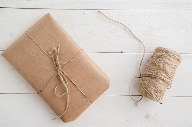 Pacote, presente embalado em papel ecológico e barbante para a embalagem na luz de fundo de madeira. a vista do topo