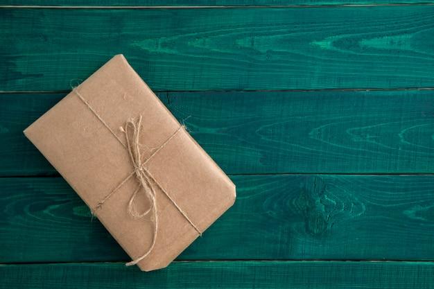 Pacote, presente embalado em papel ecológico, sobre fundo verde escuro de madeira. a vista do topo