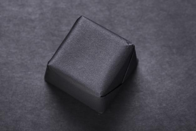 Pacote preto embrulhado para presente, pacote em fundo escuro