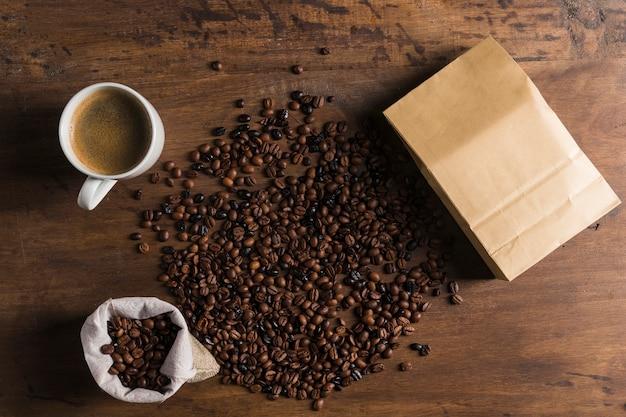 Pacote, saco e xícara perto de grãos de café