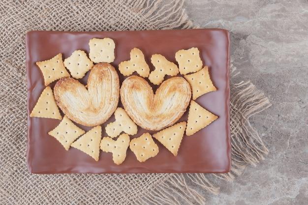Pacotes de biscoitos e biscoitos em uma travessa em mármore