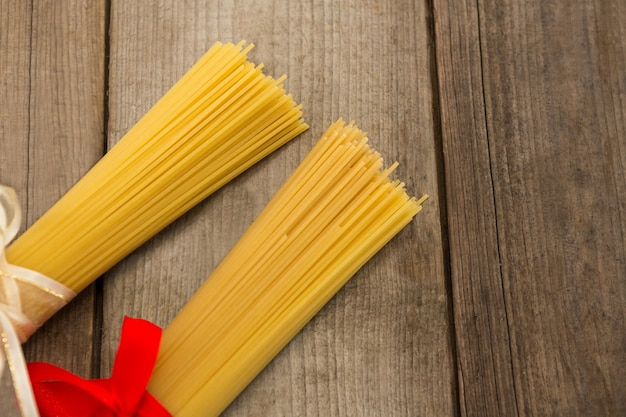 Pacotes de espaguete cru amarrados com fitas na superfície de madeira