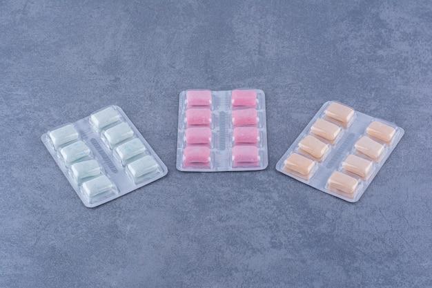 Pacotes de goma com vários sabores exibidos na superfície de mármore