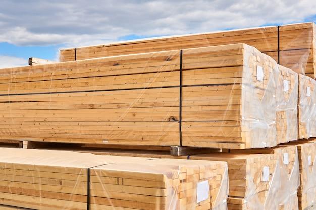 Pacotes de novas pranchas de madeira embalados para carregamento e transporte ao ar livre