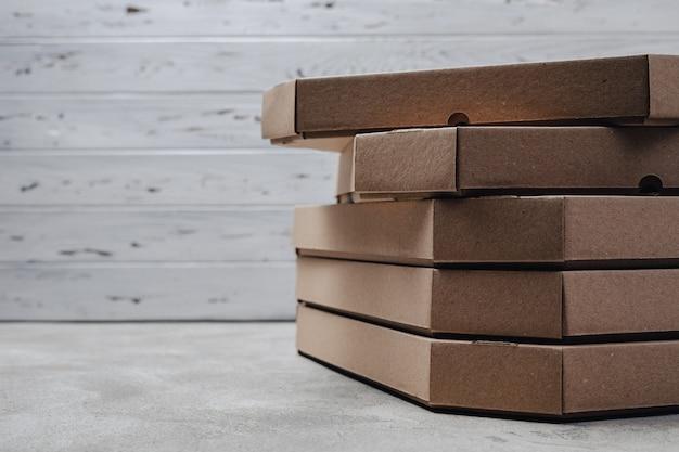 Pacotes de pizza na luz de fundo de concreto