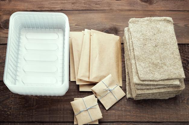 Pacotes de sementes, recipientes de plástico e tapetes de linho