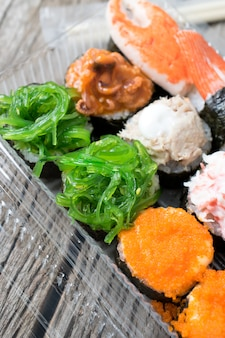 Pacotes de sushi de supermercado na mesa de madeira