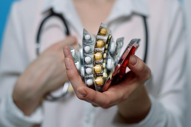 Pacotes dobrados verticalmente com pílulas diferentes na mão de uma mulher e um estetoscópio no pescoço