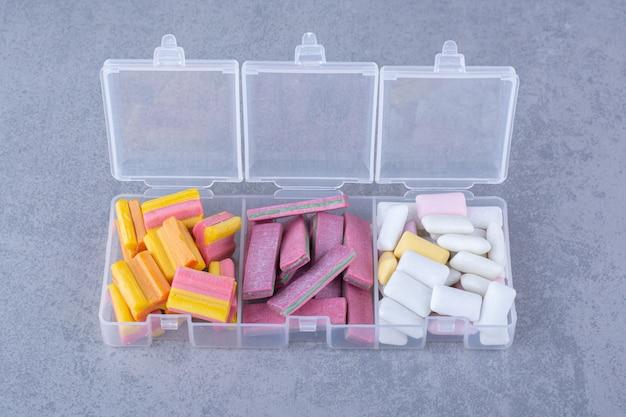 Pacotes variados de chicletes empilhados ordenadamente em pequenos recipientes na superfície de mármore