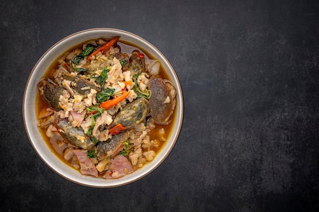 Pad ka prao kai yeow ma, comida tailandesa, manjericão mexido ovo século frito com carne de porco e presunto em fundo de textura cinza escuro com espaço de cópia para o texto