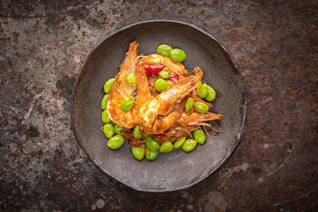 Pad ped sator goong, comida tailandesa, camarão e feijão fedorento frito com pasta de curry vermelho em placa de estilo wabi sabi em fundo de textura enferrujada, vista de cima, feijão amargo, feijão trançado, feijão fedorento