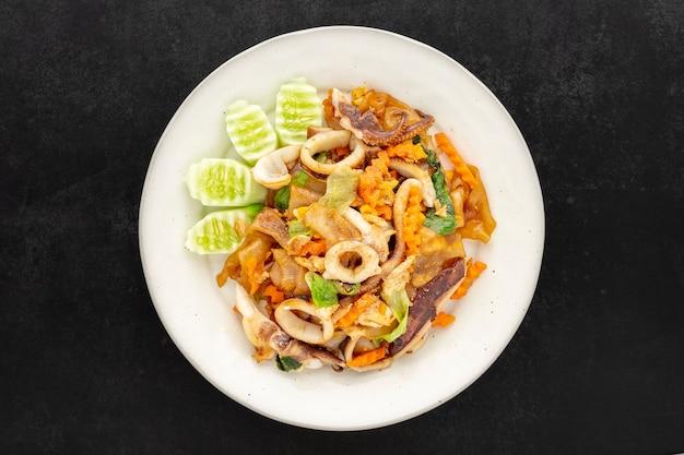 Pad see ew pla muek, comida tailandesa, macarrão de molho de soja frito com lula, ovo, alface, cenoura servida com pepino em fundo de textura de tom escuro, vista superior