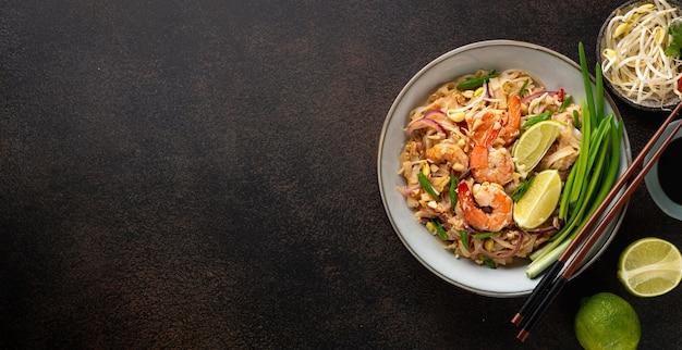 Pad thai com camarão em uma tigela de cerâmica em um fundo escuro, vista de cima, copie o espaço