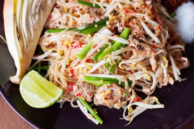 Pad thai com carne de porco em prato preto