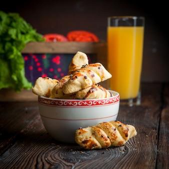 Padaria caseira de close-up com uma xícara de chá, suco de laranja e tomate na mesa de madeira