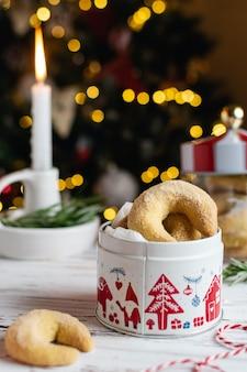 Padaria caseira de natal, biscoitos de baunilha crescente com velas, árvore de natal e bokeh