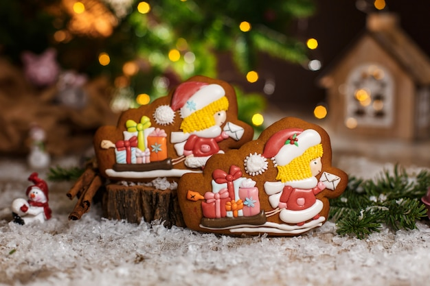 Padaria de comida tradicional de férias. carteiro de gengibre dois chirstmas e trenó com presentes na decoração aconchegante e quente com luzes de guirlanda