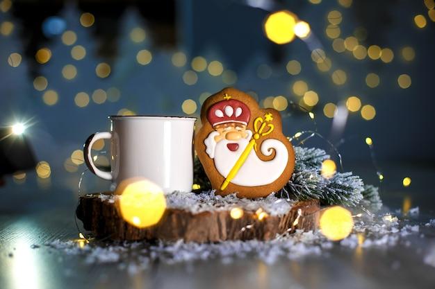 Padaria de comida tradicional de férias. velho assistente de gengibre em decoração aconchegante com luzes de guirlanda e xícara de café quente